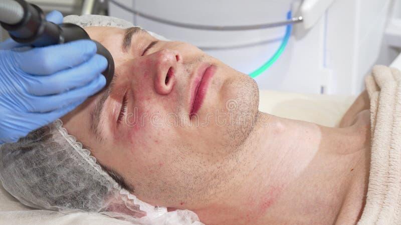 Man receiving facial ultrasound cavitation treatment by cosmetologist stock photos