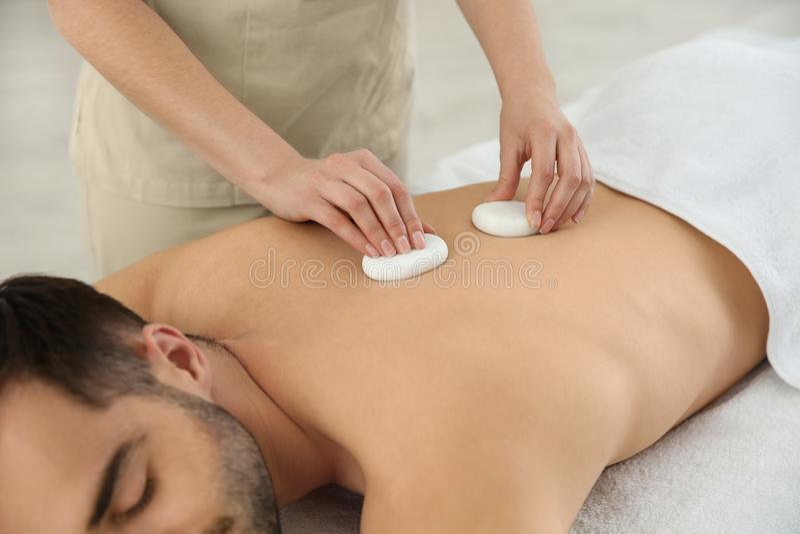 Man receiving hot stone massage in spa salon. Closeup stock photography