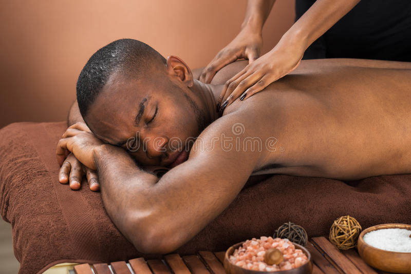 Man Receiving Massage Treatment. Close-up Of Happy African Man Receiving Massage Treatment stock photography