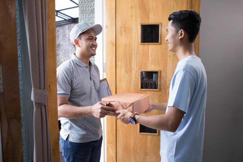 Package delivery box. Man receiving a package at home from a delivery guy royalty free stock photos