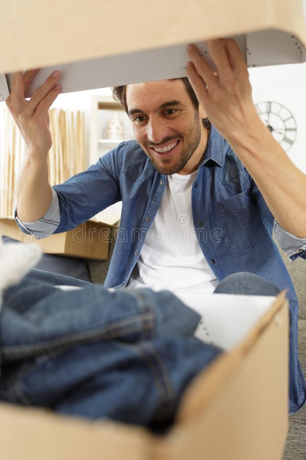 Man receiving parcel at home. Man stock photo