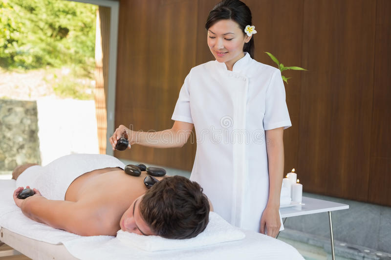 Man receiving stone massage at spa center. Handsome young men receiving stone massage at spa center royalty free stock image