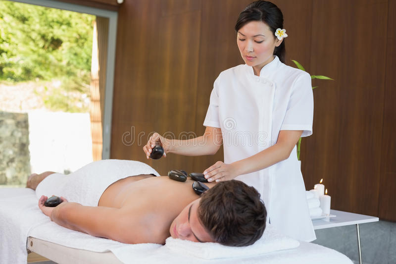 Man receiving stone massage at spa center. Handsome young men receiving stone massage at spa center royalty free stock photo