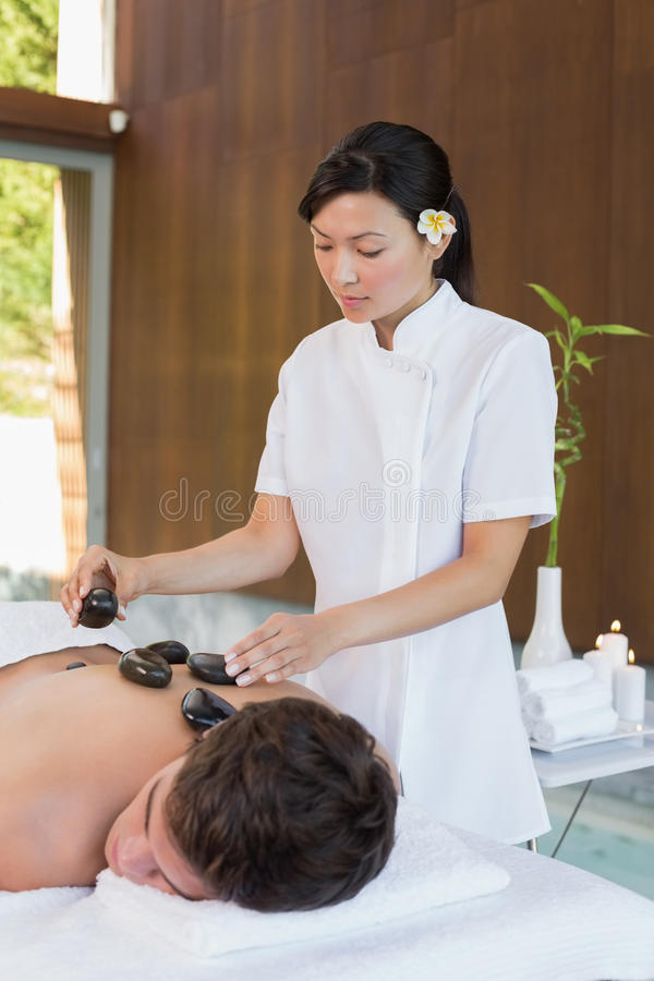 Man receiving stone massage at spa center. Handsome young men receiving stone massage at spa center royalty free stock images