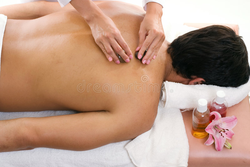 Man receiving thermal stone massage royalty free stock photography