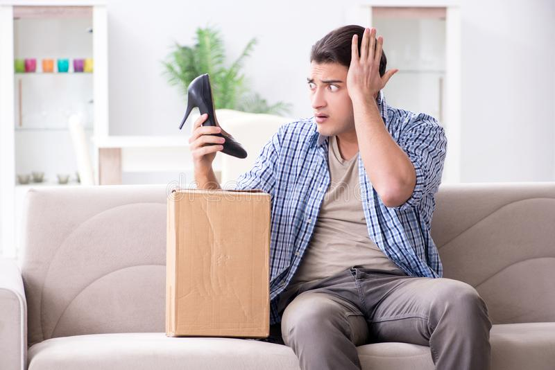 The man receiving wrong parcel with female woman shoes. Man receiving wrong parcel with female woman shoes royalty free stock images