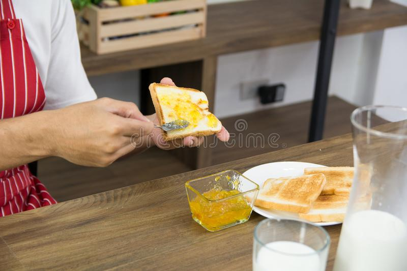 Man in red apron spreading sweet orange peel jam on toast with sun icon over table royalty free stock images