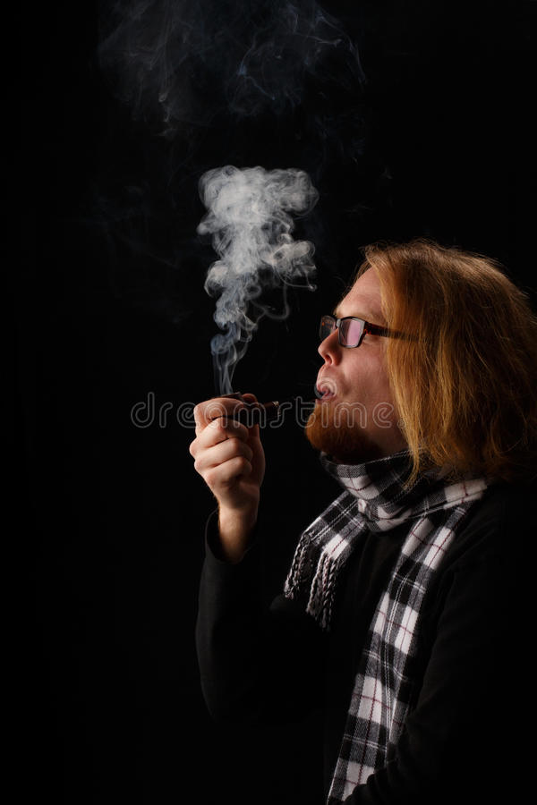 Man with red beard in chequered scarf and glasses holds tobacco stock photos