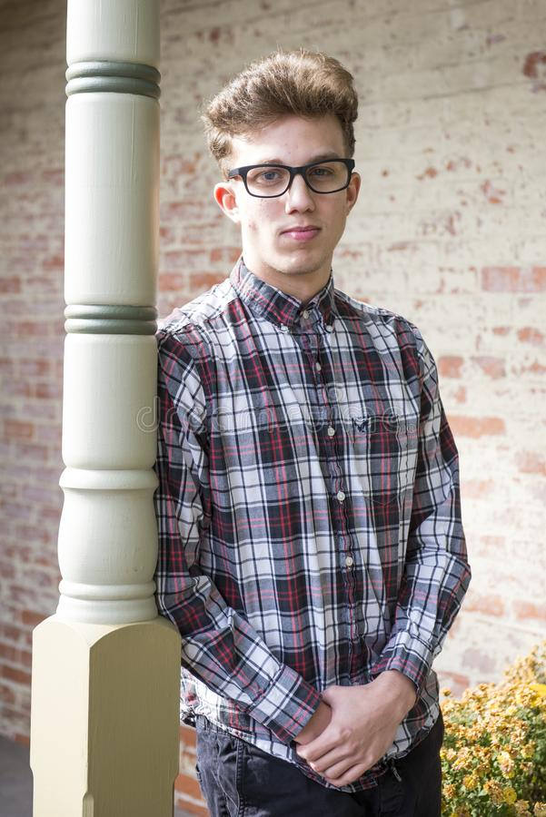 Man in Red Black and White Plaid-printed Dress Shirt Wearing Wayfarer Eyeglasses Leaning on White Wooden Post stock images