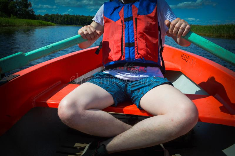 A man in a red boat, shorts and a life jacket is paddling with oars on a boat for a walk on the water of the lake river sea royalty free stock photography