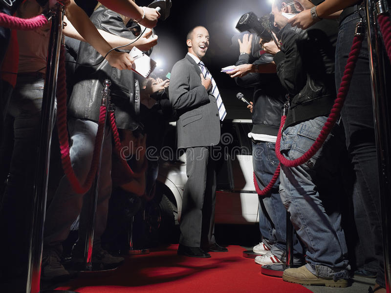Man On Red Carpet Posing In Front Of Paparazzi stock photography