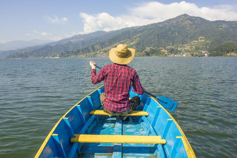 Man in a red checkered shirt and beige hat sits in a blue wooden boat with a paddle in his hands, on a lake against a background o royalty free stock images