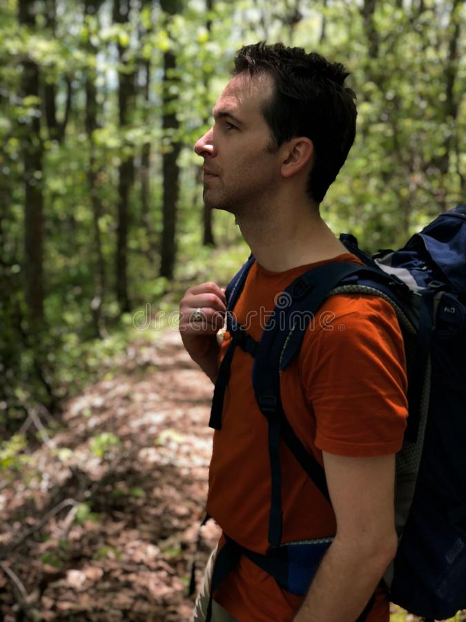 Man in Red Crew-neck Shirt Carrying Blue Hiking Backpack stock photography