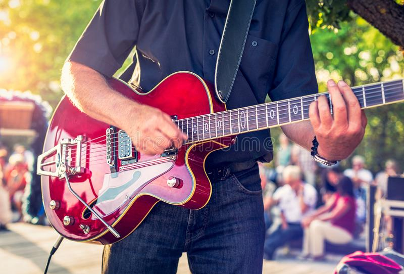 Man with a red electric guitar in the park playing a concert. Sound royalty free stock photo