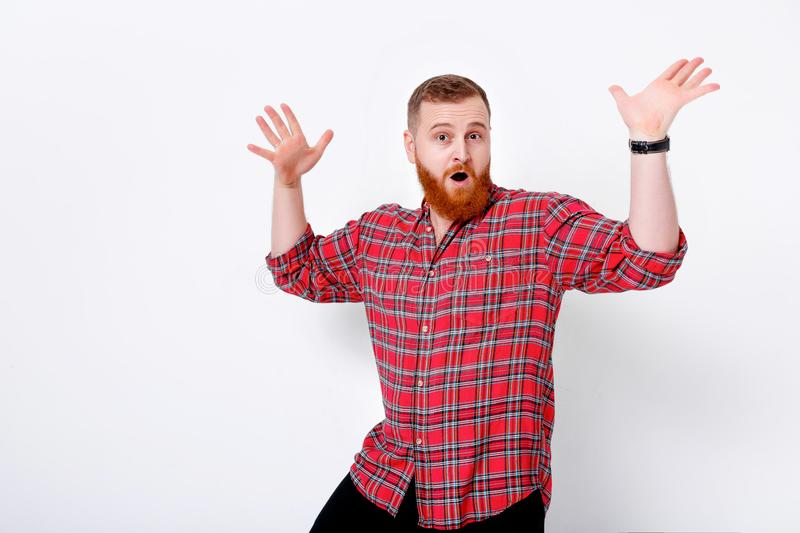 Man with red hair and beard in plaid shirt. Portrait of handsome happy man with red hair and beard in plaid shirt against white wall stock photography