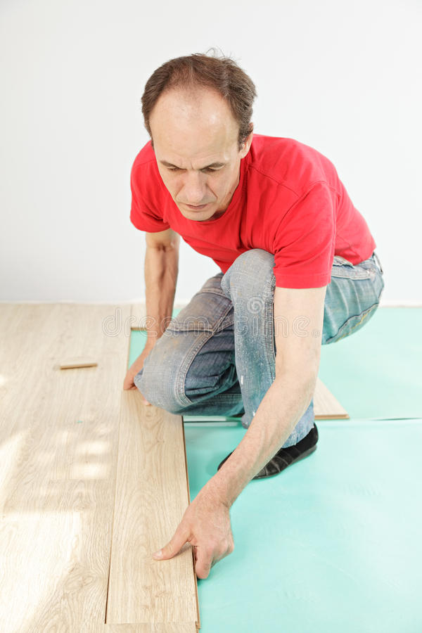 Man in red installing flooring
