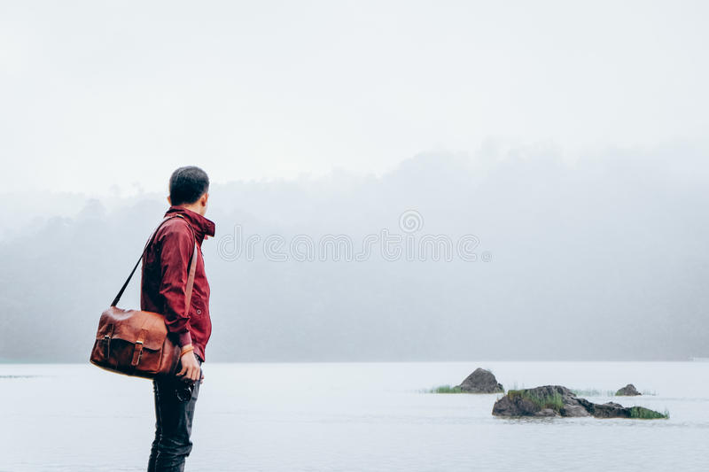 Man In Red Jacket Carrying Brown Leather Shoulder Bag Standing On Foggy Weathered Field Free Public Domain Cc0 Image
