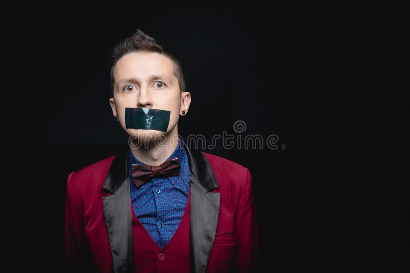 Man in red jacket with closed tape over his mouth. Black isolated background royalty free stock photo