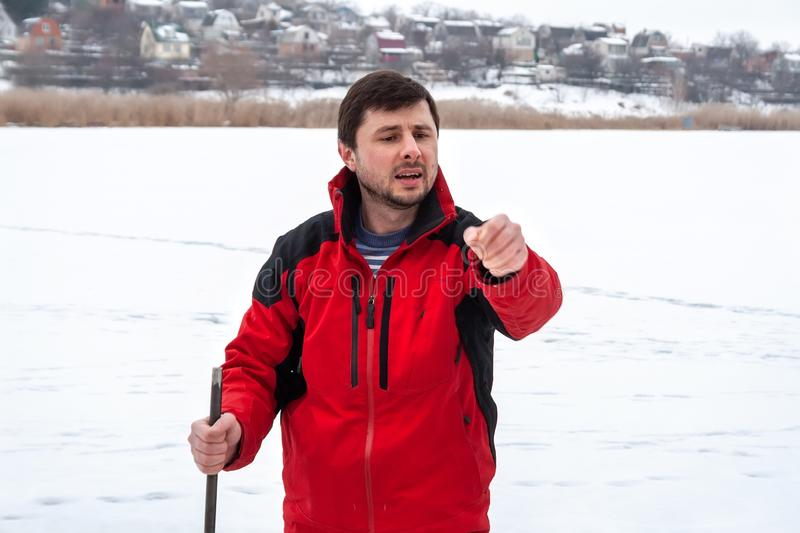 A man in a red jacket with a crowbar in his hands gives instructions, standing on a frozen river. Far beyond the river small houses can be seen stock photo