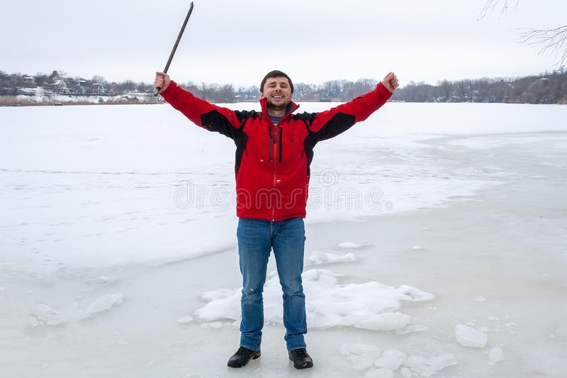 A man in a red jacket and jeans stands on a frozen river, smiles happily, raising his hands up, in one of them he holds a crowbar.  stock photography