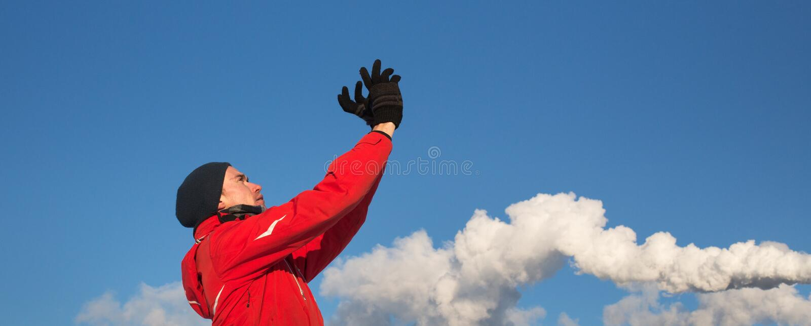 A man in red jacket looking at sky with hands holding up. Blue sky and smoke background royalty free stock images
