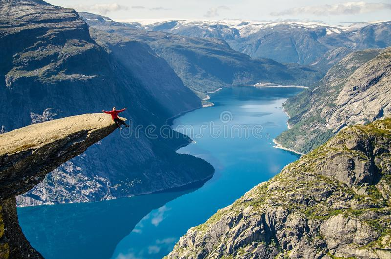 A man in a red jacket sitting on the Trolltunga rock with a blue lake 700 meters lower and interesting sky with clouds.  stock photo