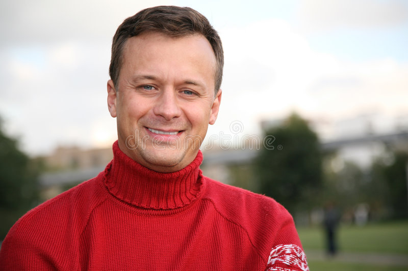 Man in red jumper 2. Smiling man in red jumper royalty free stock photography