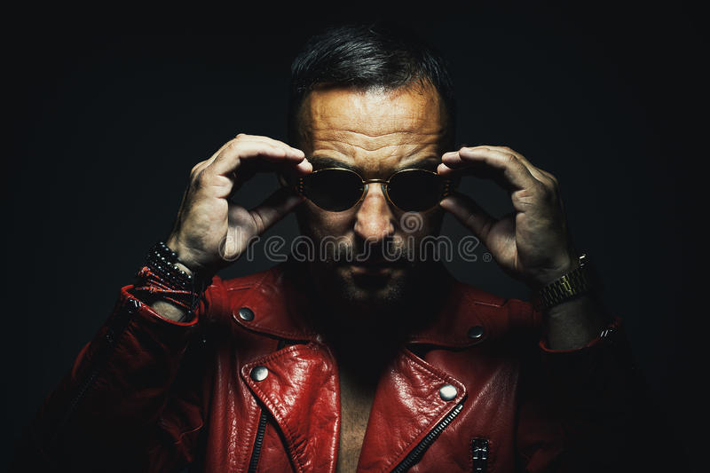 Man in Red Leather Jacket. Adult man in red leather jacket, wearing sun glasses stock images