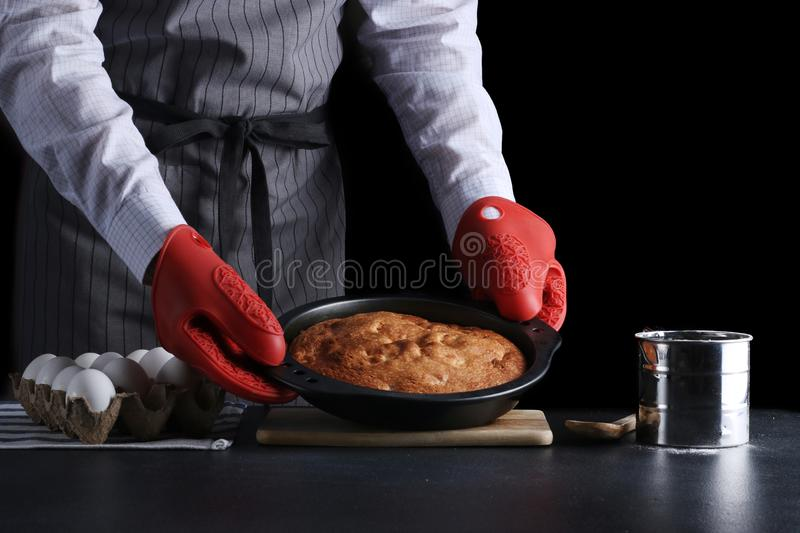 Man in red potholder holding pie dark background and isolated on black. recipe concept with ingredients on table stock image
