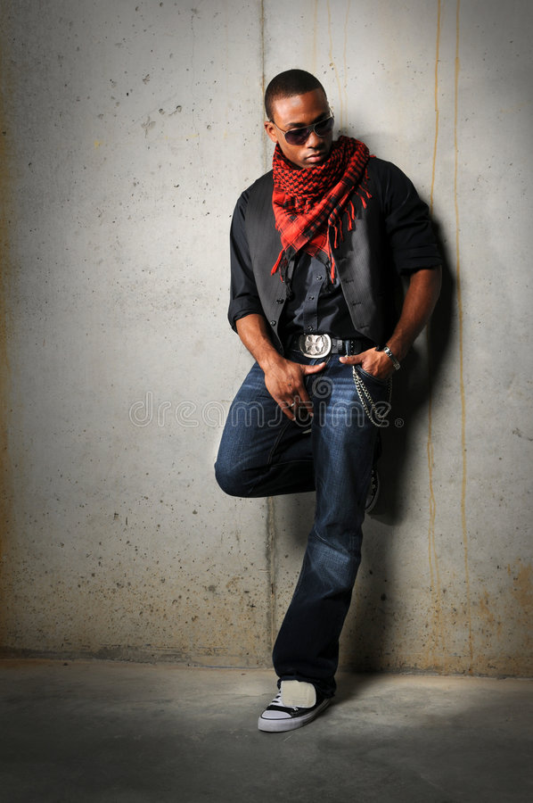 Man With Red Scarf Standing. African American man with red scarf standing against a concrete wall stock photography