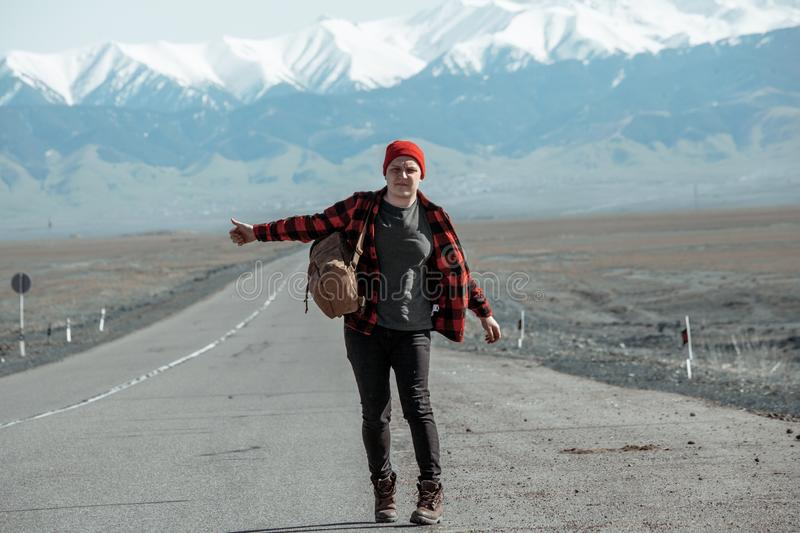 Man in shirt and backpack hitchhiking down on dusty road. Man in red shirt and backpack hitchhiking down on dusty mountain road stock photos