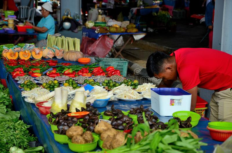 Man in red shirt behind fresh fruit vegetables stall Satok Weekend Market Kuching Sarawak Malaysia stock image