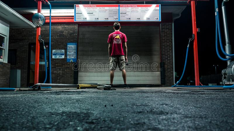 Man in Red Shirt and Brown Shorts Standing Near Wall stock photography