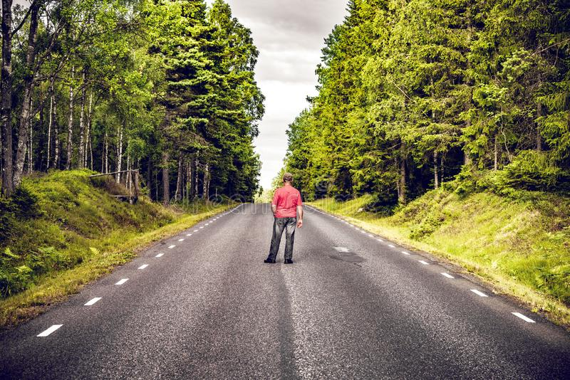 Man in a red shirt looking down an asphalt road stock photography