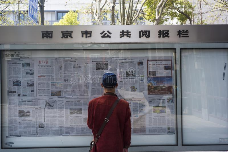 Man in red shirt looking at public reading column. An elderly man wearing a red shirt and a blue hat is looking at the public reading column on Zhonghua Road royalty free stock images