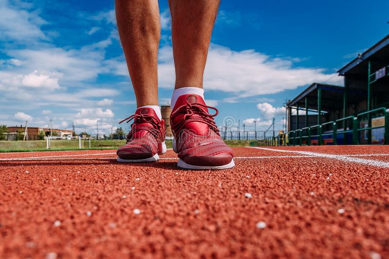 A man in red sports shoes runs on a red treadmill at the stadium in the summer, only his feet. Are close royalty free stock image