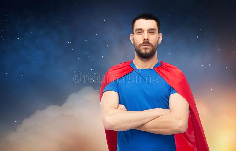 Man in red superhero cape over night sky royalty free stock photos