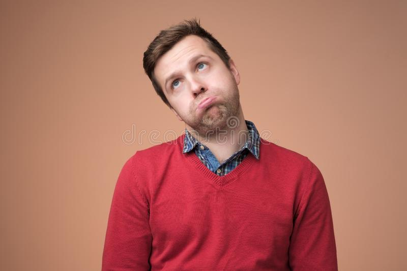 Man in red sweater puffing his cheeks, feeling fed up as heis tired royalty free stock images