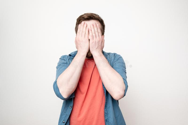 Man in a red t-shirt and blue shirt covers his face with his hands, on a white background stock photography