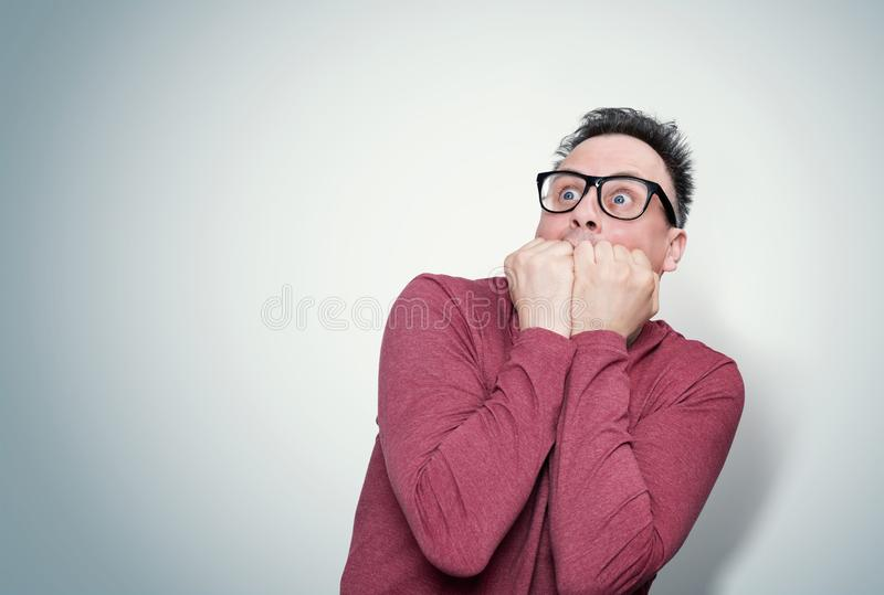 Man in a red T-shirt and glasses covering his face with his hands in horror looks at the sky. Fear concept. stock images