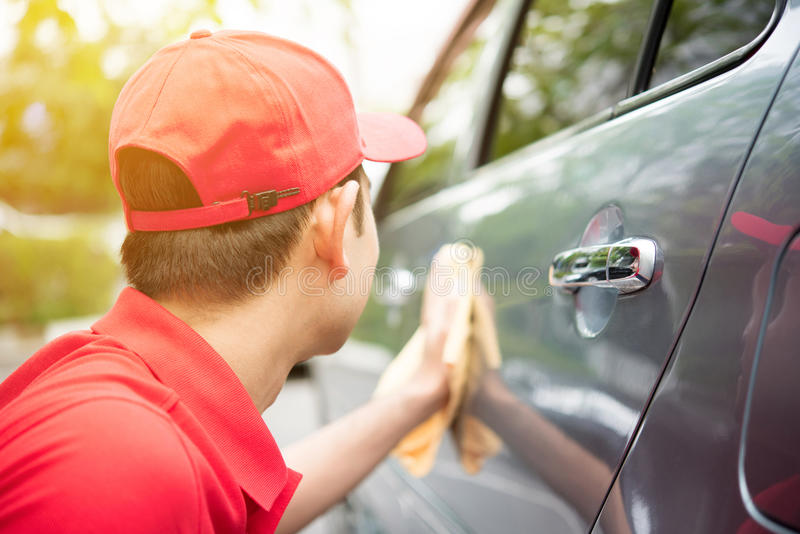 A man in red uniform cleaning car. Auto cleaning service concept royalty free stock image
