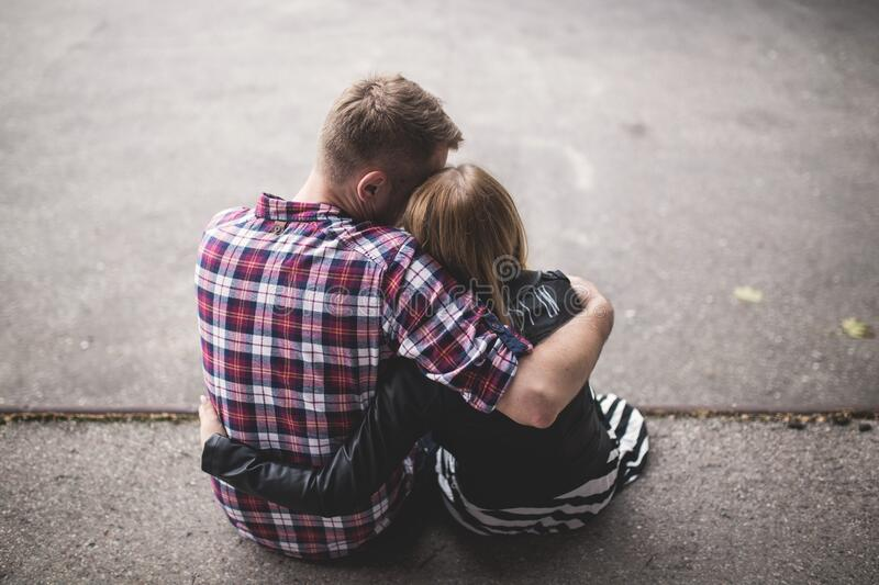 Man in Red White and Blue Check Long Sleeve Shirt Beside Woman in Black and White Stripes Shirt Hugging Each Other While Sitting o stock photos