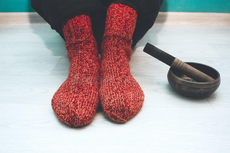 Man in a red woolen socks with a singing bowl. Man in a red woolen socks sitting on the floor in the yoga studio with a singing bowl stock photos
