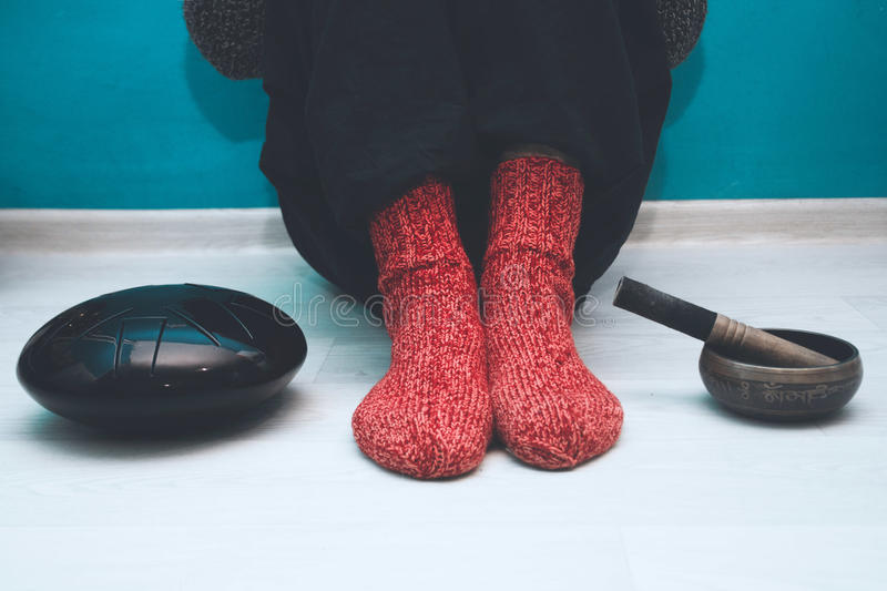 Man in a red woolen socks with a singing bowl and steel tongue drum. Man in a red woolen socks sitting on the floor in the yoga studio with a singing bowl and royalty free stock photo