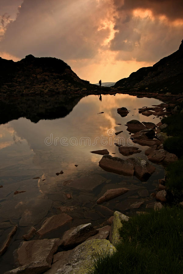 Man reflected in lake at sunset stock photo
