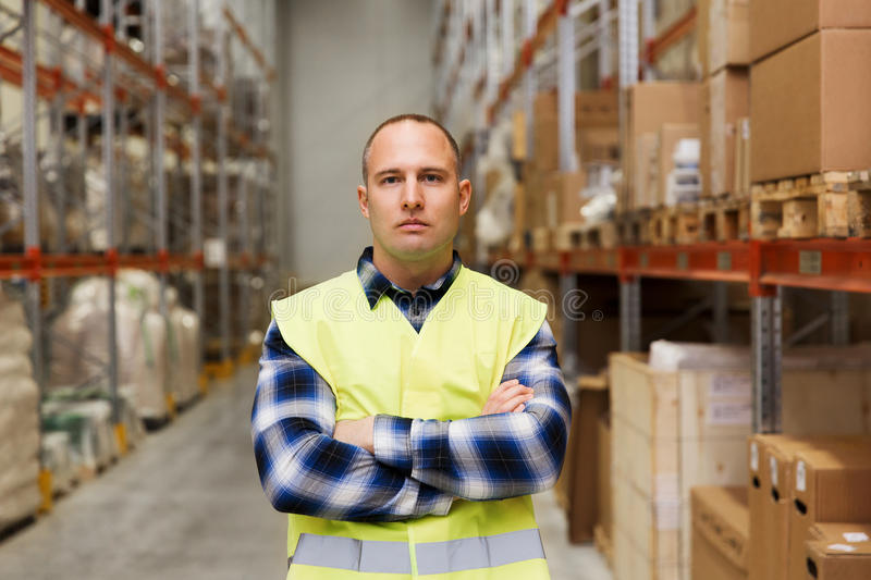Man in reflective safety vest at warehouse. Wholesale, logistic, people and export concept - man in reflective safety vest at warehouse stock images