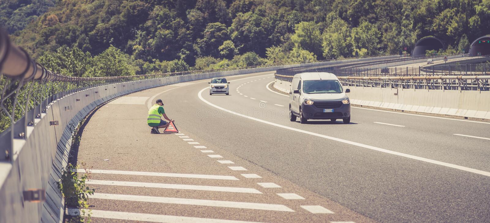 Man in reflective vest arranges a warning triangle, car breakdown on the highway stock photos
