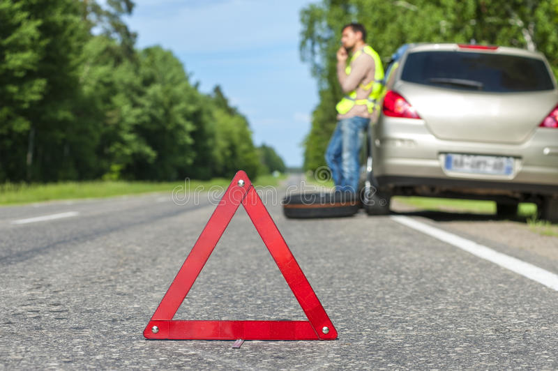 Man in reflective vest calling to a car assistance after breakdown stock photo