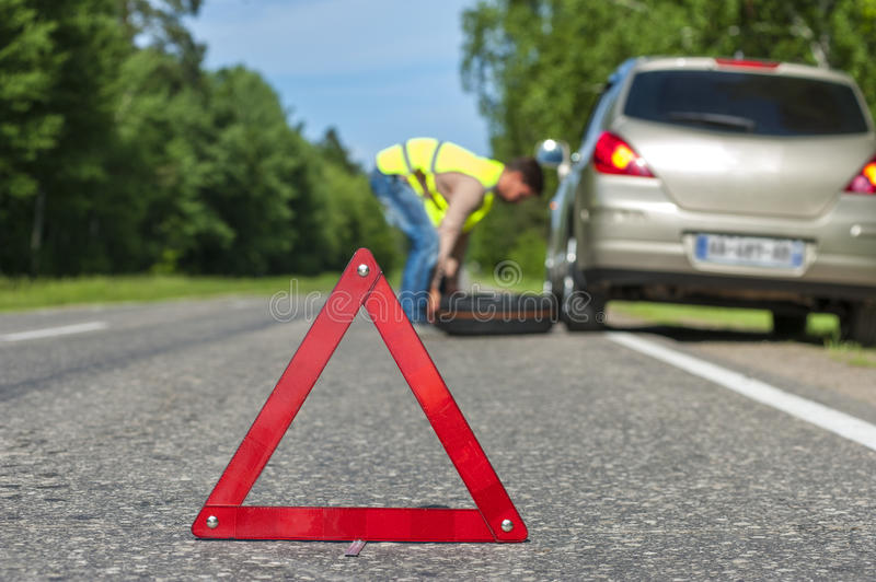 Man in reflective vest changing tire after breakdown royalty free stock photos