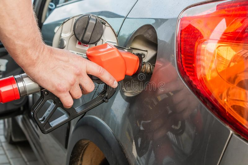 Man refueling his gray car holding red filling gun at the gas station stock photo